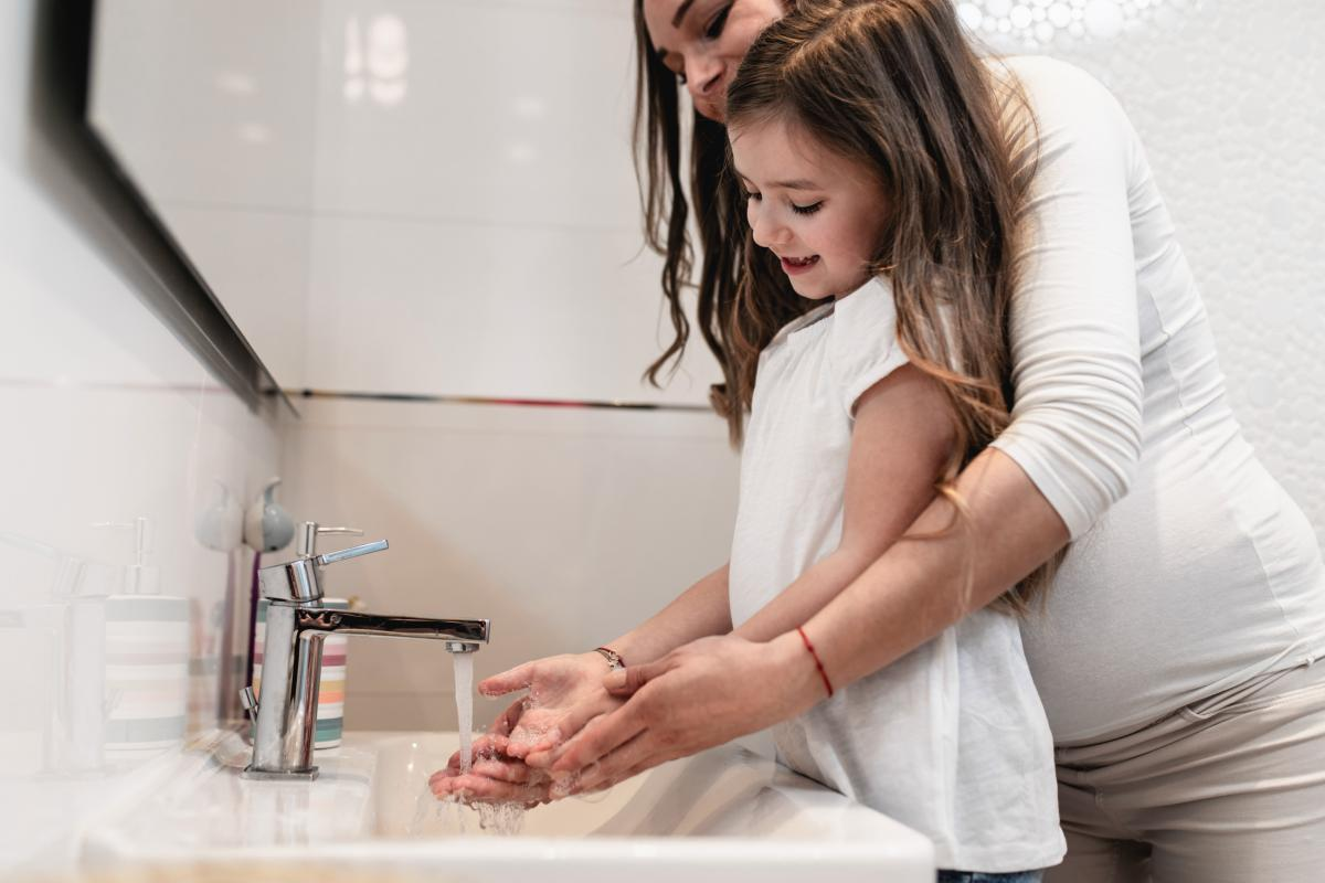 Pregnant Parent and Girl Handwashing